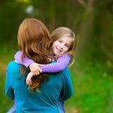 Momia que detiene a la muchacha del niño de la hija en su sonrisa de la vista posterior de los brazos Fotografía de archivo