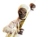 Momia que lleva a cabo una muestra en blanco aislada en blanco Fotos de archivo