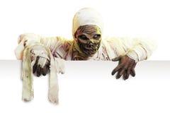 Momia que lleva a cabo una muestra en blanco aislada en blanco Foto de archivo libre de regalías