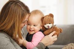 Momia y bebé felices con el oso de peluche Imagenes de archivo