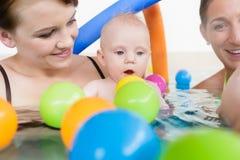 Momias y bebés que se divierten en el curso infantil de la natación fotografía de archivo