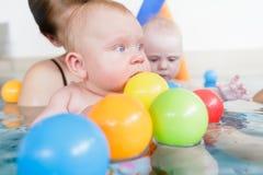 Momias y bebés que se divierten en el curso infantil de la natación imagenes de archivo