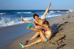 Momie avec des enfants sur une plage Image stock