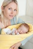 Mominnehav som hon som sovar, behandla som ett barn, som slås in upp i en täcka Arkivfoto
