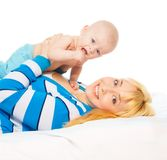 Mommy in bed with little baby. Mommy lifting happy little baby, laying with him together in the bed, isolated on white Royalty Free Stock Image