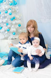 Mommy with children at New Year tree Stock Images