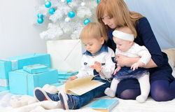 Mommy with children at New Year tree Royalty Free Stock Photos