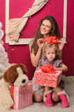 Mommy and daughter with gifts indoors Stock Images