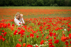 Mommy and daughter in a meadow. Young mother and her daughter having fun in a meadow full of poppy flowers during a sunny afternoon Royalty Free Stock Photos