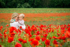 Mommy and daughter in a meadow. Young mother and her daughter having fun in a meadow full of poppy flowers during a sunny afternoon Royalty Free Stock Photo