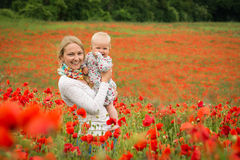 Mommy and daughter in a meadow. Young mother and her daughter having fun in a meadow full of poppy flowers during a sunny afternoon Stock Photography