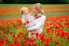Mommy and daughter in a meadow. Young mother and her daughter having fun in a meadow full of poppy flowers during a sunny afternoon Royalty Free Stock Images