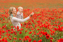 Mommy and daughter in a meadow. Young mother and her daughter having fun in a meadow full of poppy flowers during a sunny afternoon Stock Photos