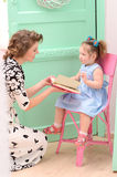 Mommy and daughter reading book stock images