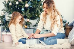 Mommy and daughter wrapping gifts Stock Image