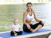 Mommy daughter yoga. Mother daughter Yoga performed on a dock by the lake Royalty Free Stock Photography
