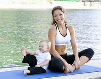 Mommy daughter yoga. Mother daughter Yoga performed on a dock by the lake Royalty Free Stock Photo