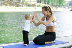 Mommy daughter yoga. Mother daughter Yoga performed on a dock by the lake Stock Photos