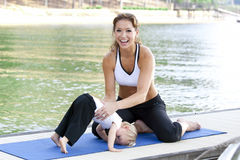 Mommy daughter yoga. A mother and daughter do some yoga on a dock by the lake Stock Photo