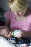 Mommy feeding baby. With a small bottle Stock Photo