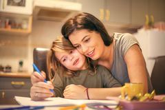 Mommy helping me to schoolwork. Close up image of mother and daughter Royalty Free Stock Images