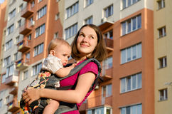 Mommy holding infant son in rucksack outdoors. Young smiling mommy holding her infant son in ergonomic rucksack on background of multistorey house outdoors royalty free stock images