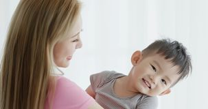 Mommy hug her son. And smile happily at home stock image