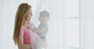Mommy hug her son. And smile happily at home stock photo