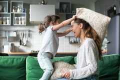 Mommy and kid daughter having pillow fight playing together. Mommy and kid daughter having pillow fight together, young babysitter nanny playing funny game with royalty free stock image