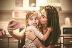 Mommy kissing me for self portrait. Mother and daughter using smart phone Royalty Free Stock Images