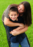 Mommy kissing son. Pretty mommy kissing her cute son on the cheek royalty free stock images