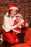 Mommy and little son in christmas festive attires. Happy young mommy and her little child in christmas festive attires in red and white indoors Royalty Free Stock Photography