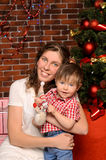 Mommy and little son at christmas tree. Smiling young mommy and her little son at christmas tree indoors Royalty Free Stock Photo