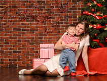 Mommy and little son at christmas tree. Smiling young mommy and her little son at christmas tree indoors with space for text stock photos