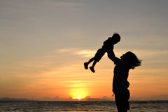 Mommy love. Silhouette of mommy and small girl on the beach at dusk Stock Image