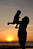 Mommy love. Silhouette of mommy and small girl on the beach at dusk Stock Images