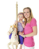 Mommy, Me and a Carousel Horse. An adorable 2-year-old on a carousel horse posing with her mother.  Focus on Mom.   On a white background Stock Photos