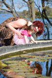 Mommy Moments. A mother looks into a pond with her one years old baby. The mother and daughter are multiracial family Royalty Free Stock Photos