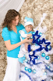 Mommy and son adorning christmas tree. Young mommy and little son in costume and hat adorning christmas tree in blue and white indoors Royalty Free Stock Images