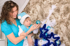 Mommy and son adorning christmas tree. Young mommy and little son in costume and hat adorning christmas tree in blue and white indoors stock images
