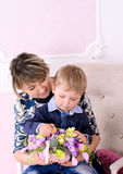 Mommy and son with basket of flowers. Young mommy and little son with basket of flowers indoors stock images