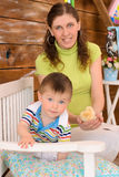 Mommy and son with chickens on bench. Young mommy and little son with chickens on bench indoors royalty free stock image