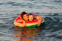 Mommy and son swimming together. In the sea with inflatable ring which looks like watermelon. They smiling and looking into the camera Royalty Free Stock Image