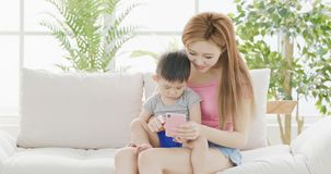 Mommy use phone with son. On sofa at home Stock Images