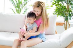 Mommy use phone with son. On sofa at home stock photography