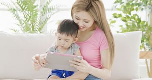 Mommy use tablet with son. Mommy use digital tablet with son on sofa at home Royalty Free Stock Photo