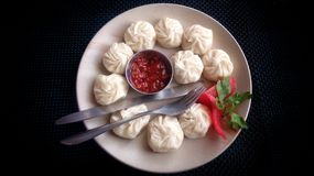 Momo on a plate with sauce. A Momo on a plate with sauce stock photos