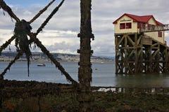 Mompelt at low tide Reddingsboothuis en pijler stock foto's