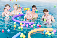 Moms and babies playing at infant swimming class Stock Photos