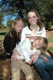 Moms and Daughters. A mom sits outside in a park with her two beautiful daughters spending time with her. Family spending time together Stock Image